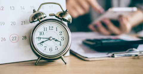 datum kalender en wekker met zakelijke vrouw hand berekenen